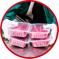 Image of a food handler holding four sealed plastic containers of food.