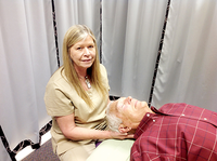 Bill Gillogly lies on his back on a massage table as his wife, Gail, holds his head at their business, Advanced Massage Studios.