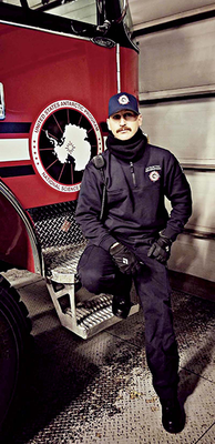 Buddy Pearce stands next to a fire truck.