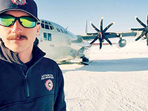 Buddy Pearce stands in front of a plane on the snow in Antarctica.
