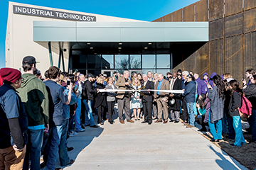 Francis Tuttle Technology Center board members and dignitaries cut the ribbon for the Industrial Technology Center while students watch.