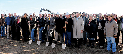 Men wearing hard hats pose with shovels in a groundbreaking ceremony. Other people stand around them.