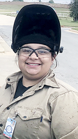 Justine Talmadge, wearing a welding hat with the hood flipped up and safety glasses, looks into the camera.