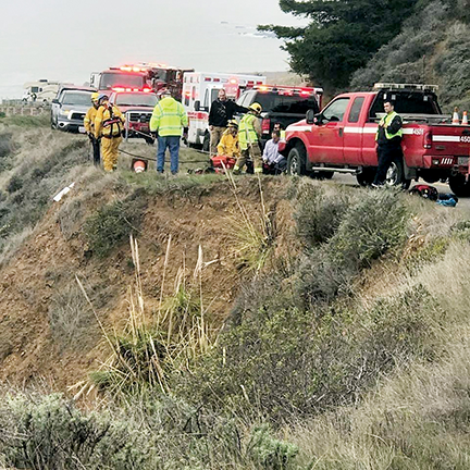 California firefighters prepare ropes so they can descend a cliff to rescue a man in a car that drove over the cliff.
