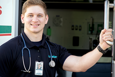 EMS Hunter Poston stands in the doorway of a LifeNet ambulance.