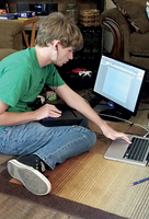 Kieran Niles uses a computer and the skills he learned in the Autry Tech graphic arts program to capture and edit videos for his church.