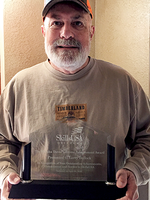 Larry Bullock holds the plaque he received for the SkillsUSA Marsha Daves Lifetime Achievement Award.