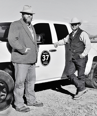 Marcus Heilman and Tyler Matthesen of Section 37 Surveying and Mapping stand next to a company truck.