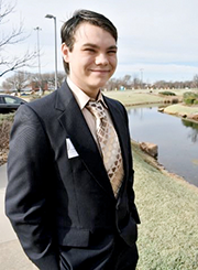 Skyler Riggle wearing a dark suit with a patterned tie in shades of brown.