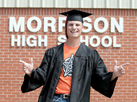 """Trevor Hughes in his high school graduation cap and gown standing in front of a brick wall with a sign on it that reads, """"Morrison High School."""""""