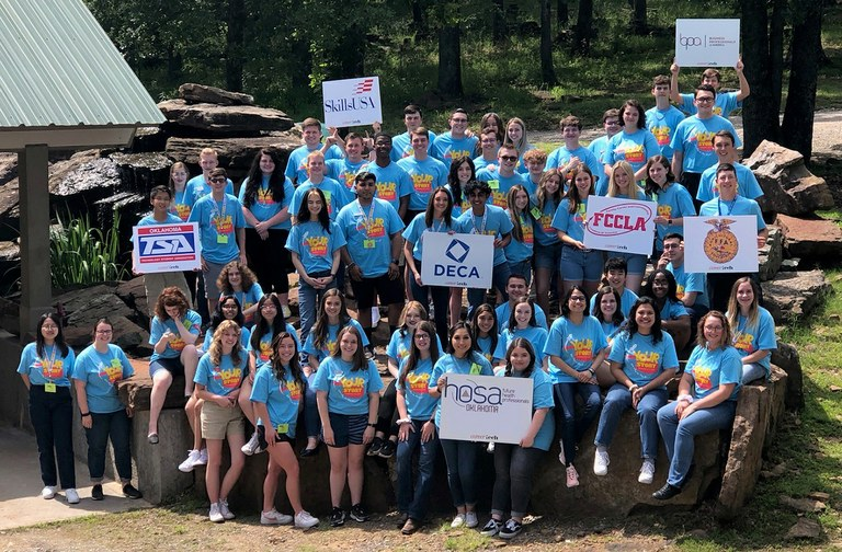 CareerTech student organization officers hold up their CTSO signs at Camp Tulakogee during CareerTech University.