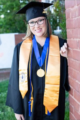 Kaydee Clark poses next to a brick wall in her graduation cap and gown.