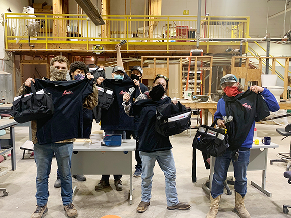 Mid-Del Technology Center students hold up black golf shirts, wrenches and black tool bags they received from Locke Supply. They are standing in a workroom.