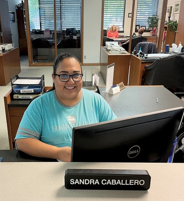 Sandra Caballero sits at a desk behind a nameplate with her name on it.