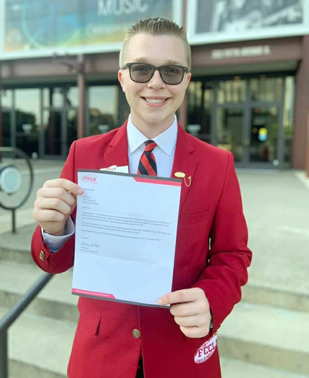 Oklahoma FCCLA member Zeb Kelly, Morrison Public Schools, wears his red FCCLA blazer and holds up his national officer election letter.